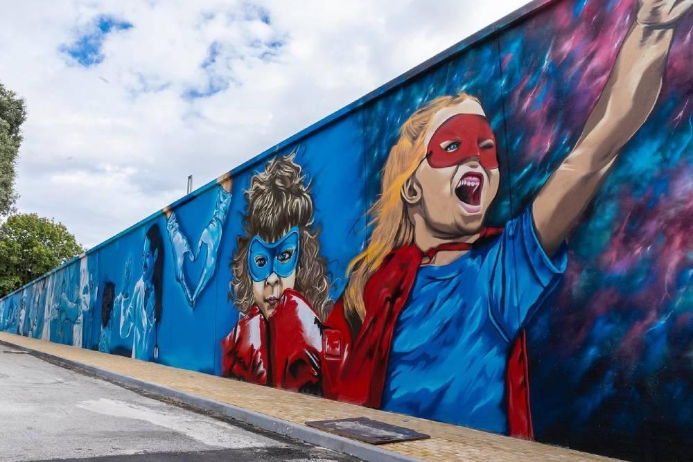 dipinto su muro principalmente di colore blu, raffigurante due bambini con la maschera e alcuni infermieri