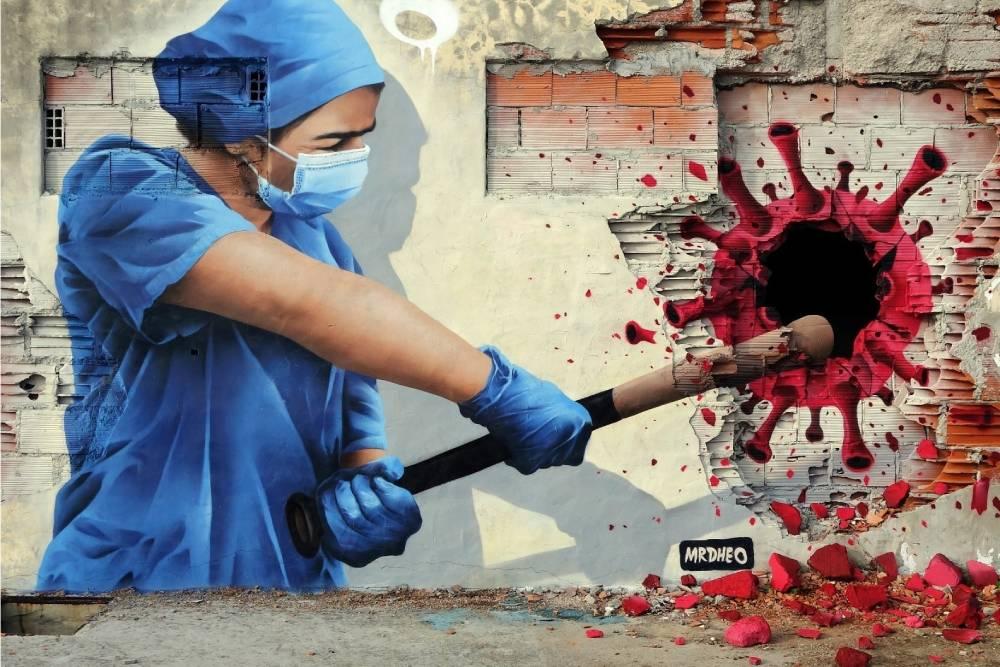 dipinto su muro raffigurante una infermiera con una mazza da baseball che colpisce una rappresentazione iconografica del virus