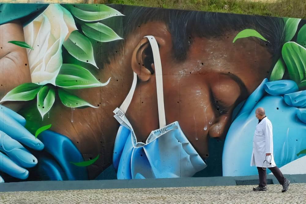 dipinto su muro rappresentante un'infermiera esausta, passeggia nella fotografia un medico che guarda l'opera